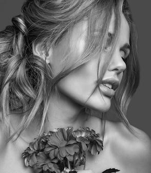 Retrato da moda beleza de modelo jovem loira com maquiagem natural e pele perfeita com flores brilhantes posando