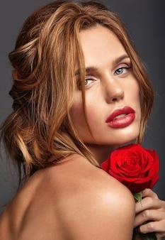 Retrato da moda beleza de modelo jovem loira com maquiagem natural e pele perfeita com linda rosa posando
