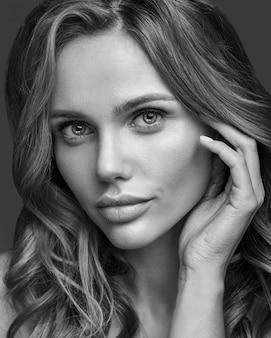 Retrato da moda beleza de modelo jovem loira com maquiagem natural e pele perfeita posando. tocando seu cabelo