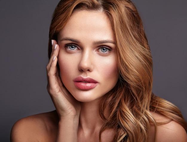 Retrato da moda beleza de modelo jovem loira com maquiagem natural e pele perfeita posando. tocando seu rosto