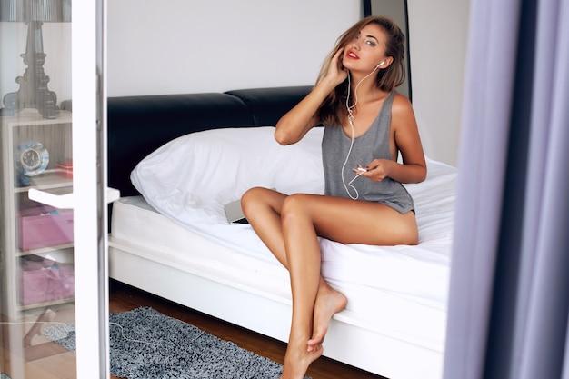 Retrato da moda brilhante da bela mulher sedutora em roupas da moda sensuais, jovem modelo atraente com corpo tonificado esportivo posando quarto branco. clima de férias de verão. música em fones de ouvido.