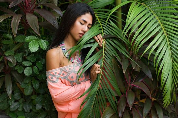 Retrato da moda da atraente mulher asiática, posando no jardim tropical. usando vestido boho e acessórios elegantes.