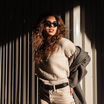 Retrato da moda da bela jovem elegante com cabelo encaracolado e óculos de sol numa camisola vintage com casaco ao ar livre à luz do sol