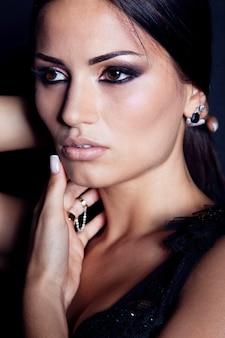 Retrato da moda da bela jovem morena com maquiagem brilhante, sobre fundo preto.