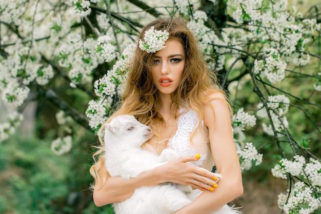 Retrato da moda da bela jovem segurando um cordeiro pequeno no jardim florido de primavera