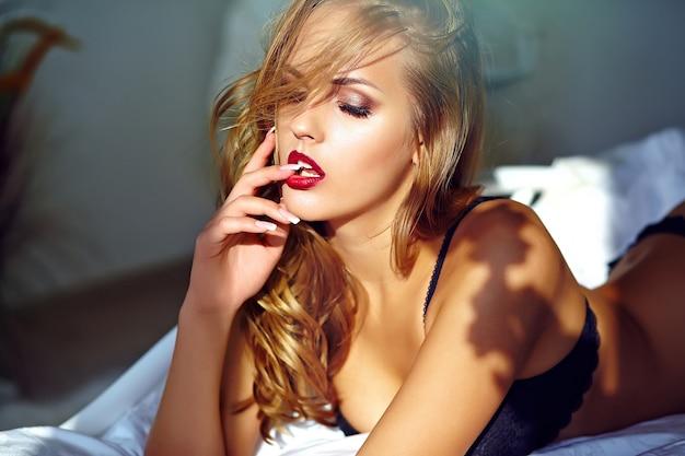 Retrato da moda da bela modelo adulto jovem loira sexy vestindo lingerie erótica preta, deitada na cama ao pôr do sol