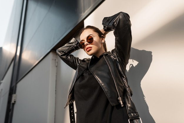 Retrato da moda da bela modelo feminina com óculos de sol em elegantes roupas pretas, com jaqueta de couro na cidade na luz do sol. garota fashion