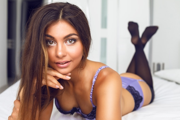 Retrato da moda da bela mulher sensual com corpo perfeito e lingerie de seda sexy, aproveite a manhã e relaxe no grande quarto branco.