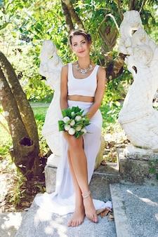Retrato da moda da bela noiva criativa, segurando um buquê de lótus exótico, vestindo uma roupa de casamento elegante e incomum e um grande colar de diamantes.