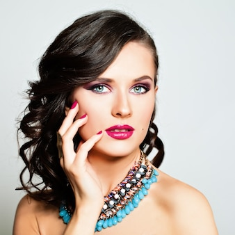 Retrato da moda da beleza. mulher bonita com maquiagem e penteado. cabelo cacheado, lábios rosados sensuais, unhas coloridas, sombra para os olhos