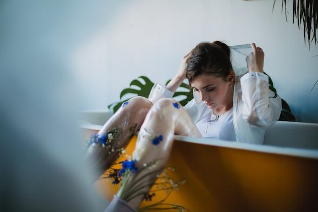 Retrato da moda da garota em roupas de tendência de plástico. estilo eco. modelo, mentindo, em, banho