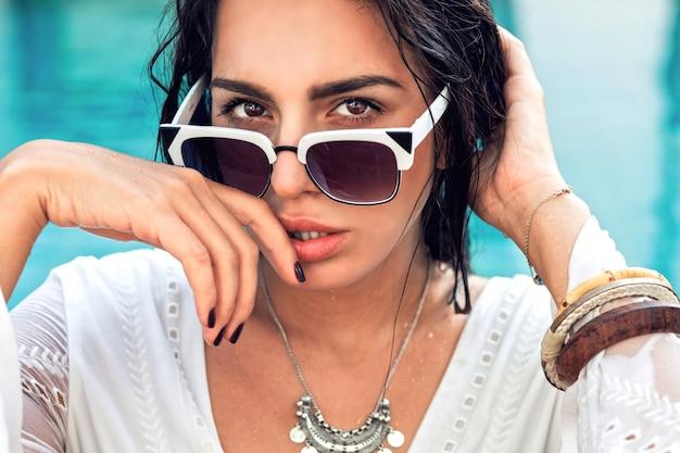 Retrato da moda da incrível mulher sensual com corpo bronzeado perfeito, posando em óculos de sol da moda na piscina