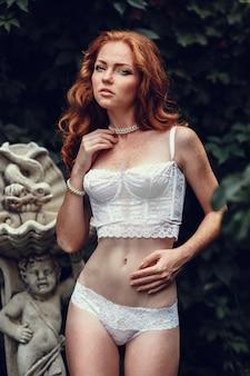 Retrato da moda da jovem e bela mulher sexy com cabelo vermelho longo ondulado. menina bonita no sutiã branco ou lingerie no jardim de verão. estilo de moda em tons retrato de cores.