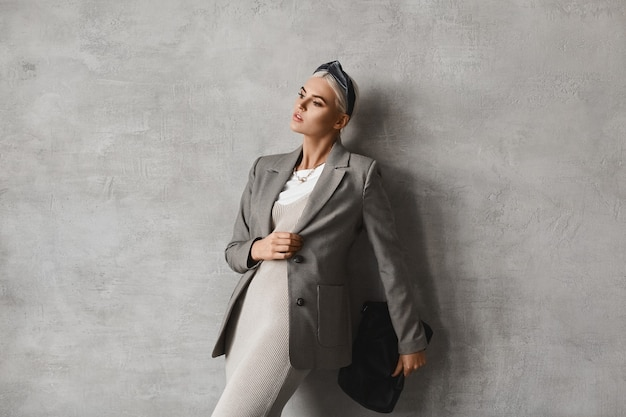 Retrato da moda da jovem elegante em roupa da moda posando dentro de casa