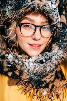 Retrato da moda da jovem garota feliz em copos, embrulhado no lenço marrom coberto de neve