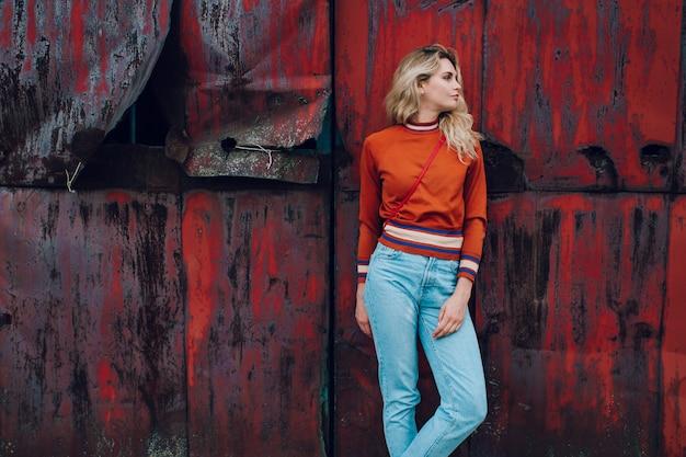 Retrato da moda da jovem loira ao longo da parede de metal enferrujado
