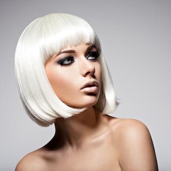Retrato da moda da jovem mulher bonita com penteado bob e maquiagem preta dos olhos
