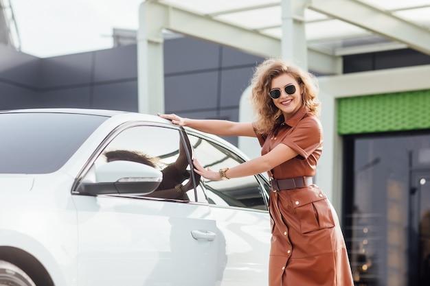 Retrato da moda da jovem mulher em um vestido ao ar livre perto de um carro branco