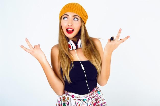 Retrato da moda da linda loira dj hipster garota segurando seus cabelos, vestindo roupa sexy brilhante e grandes fones de ouvido brancos.