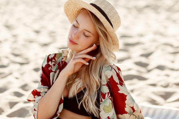 Retrato da moda da linda mulher loira com maquiagem natural, descansando na praia ensolarada. usando chapéu de palha. férias e clima de férias.
