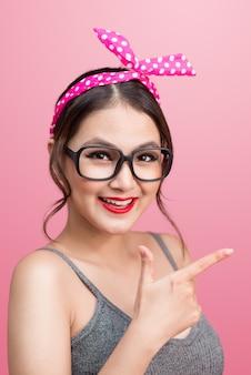 Retrato da moda da menina asiática com óculos de sol em pé sobre fundo rosa.