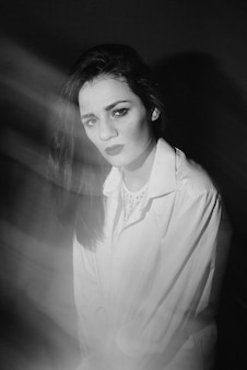 Retrato da moda da menina morena caucasiana, posando de camisa branca