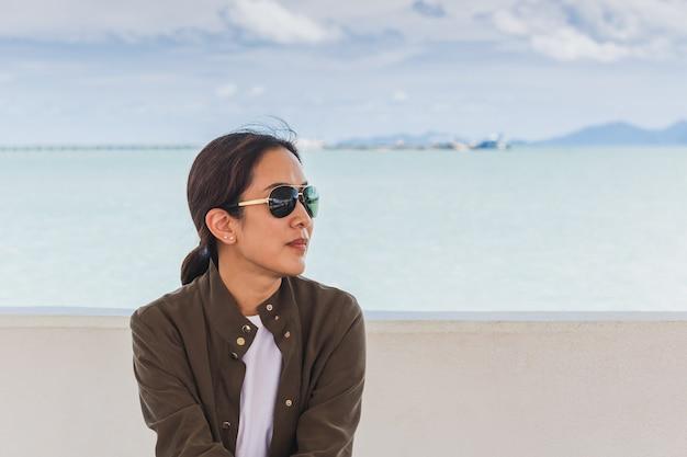 Retrato da moda da mulher asiática com óculos de sol nas férias de verão.