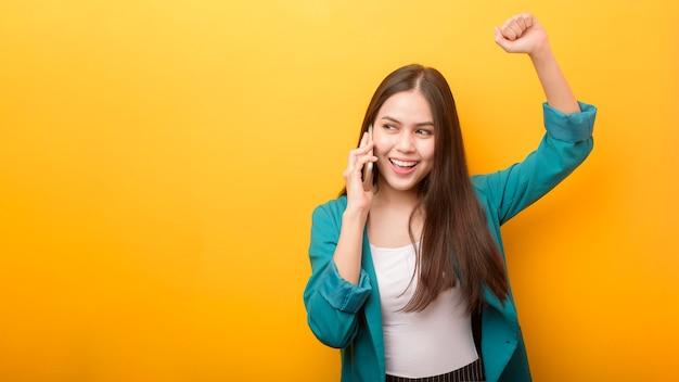 Retrato da moda da mulher bonita de terno verde, usando o celular em amarelo