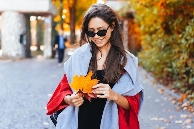 Retrato da moda da mulher bonita no parque outono