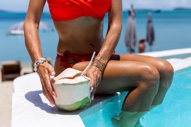 Retrato da moda da mulher caucasiana de biquíni na piscina azul de férias