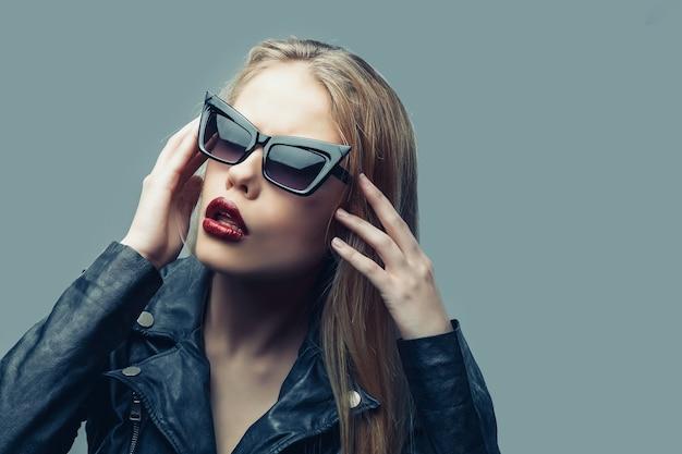 Retrato da moda da mulher de jaqueta de couro preta, óculos escuros, lábios vermelhos.