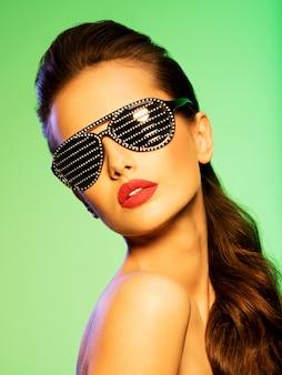 Retrato da moda da mulher de óculos escuros pretos com diamantes. cores saturadas