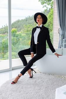 Retrato da moda da mulher de terno preto, gravata borboleta e chapéu em villa de luxo