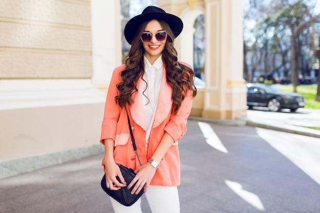Retrato da moda da mulher elegante com roupa casual, andando na cidade.