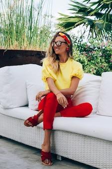 Retrato da moda da mulher elegante em calças vermelhas, blusa amarela, óculos escuros e lenço na cabeça.