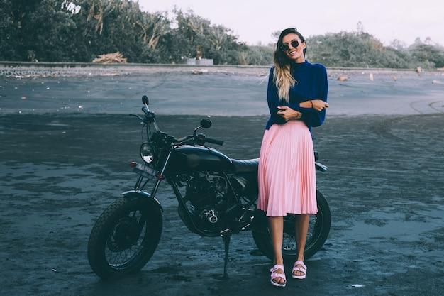 Retrato da moda da mulher elegante em óculos de sol, blusa azul e saia rosa, fica de bicicleta preta na praia de areia preta.