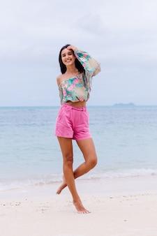 Retrato da moda da mulher elegante em top de manga comprida de impressão colorida e shorts rosa na praia, fundo tropical.
