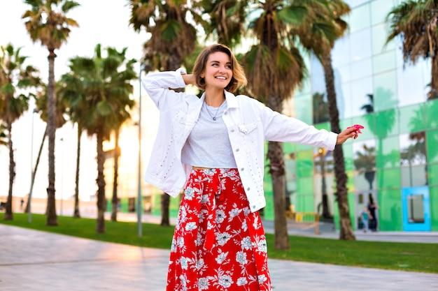 Retrato da moda da mulher elegante, posando na rua de barcelona, palmas ao redor, óculos de sol neon, clima de viagem, roupa casual hipster, alegria, espírito livre.