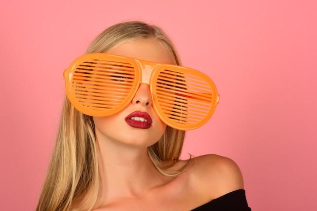 Retrato da moda da mulher em óculos de sol laranja listrados de plástico