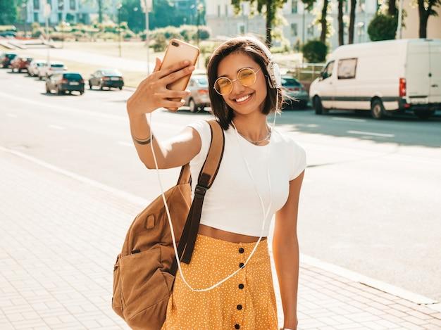 Retrato da moda da mulher jovem hippie elegante andando na rua. garota fazendo selfie. modelo sorridente desfrutar de seus fins de semana com mochila. mulher ouvindo música através de fones de ouvido