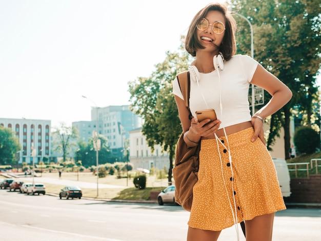 Retrato da moda da mulher jovem hippie elegante andando na rua. garota vestindo roupas da moda bonito. modelo sorridente desfrutar de seus fins de semana, viajar com mochila. mulher ouvindo música através de fones de ouvido