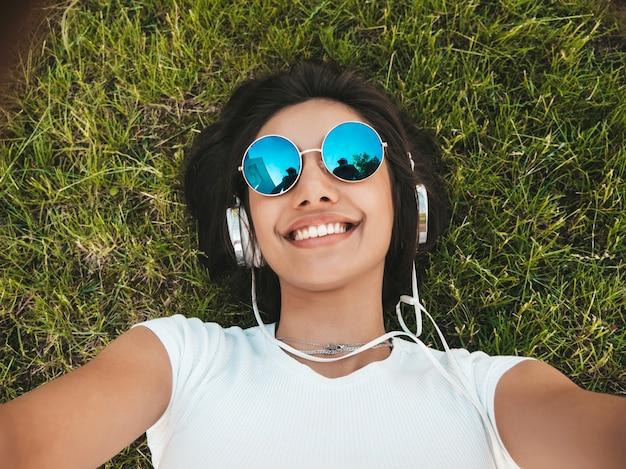 Retrato da moda da mulher jovem hippie elegante deitado na grama do parque. garota usa roupa da moda. mulher ouvindo música através de fones de ouvido.