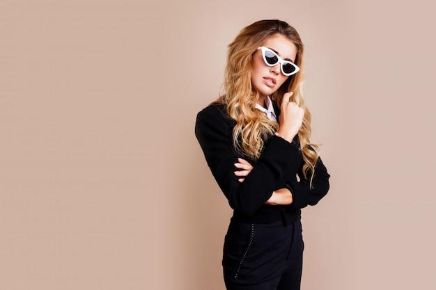 Retrato da moda da mulher loira linda elegante casaco preto casual, posando na parede bege. óculos retrô brancos. alta moda.