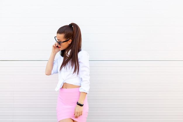 Retrato da moda da mulher muito sorridente em óculos de sol, falando no smartphone contra a parede cinza.