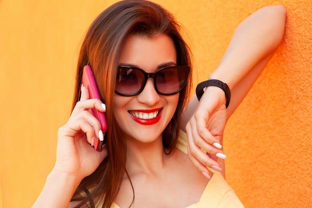 Retrato da moda da mulher muito sorridente em óculos de sol falando no smartphone