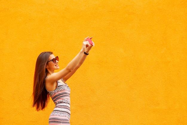 Retrato da moda da mulher muito sorridente em óculos de sol fazendo selfie pelo smartphone