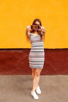 Retrato da moda da mulher muito sorridente em óculos de sol, fazendo selfie pelo telefone contra a parede laranja. pulseira de fitness na mão. cabelos voadores