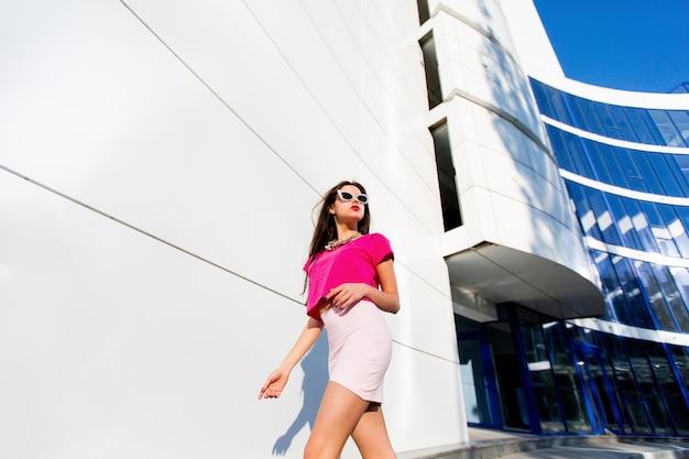 Retrato da moda da mulher sexy brilhante de glamour no top rosa e saia com pernas longas perfeitas, caminhando contra o meio urbano moderno.