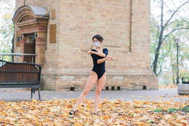 Retrato da moda da mulher sexy na máscara facial e uma roupa no outono park. pandemia, vírus, coronavírus