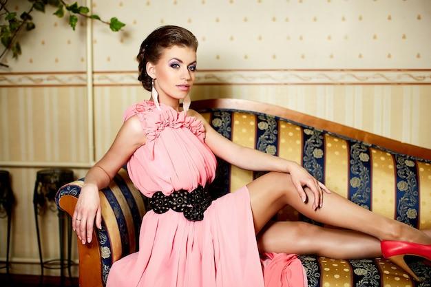 Retrato da moda da senhora bela jovem modelo feminino com penteado no vestido rosa brilhante no interior, sentado no sofá